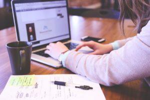 Personne utilisant son ordinateur. A côté se trouve une tasse de café, une feuille de papier et un bic.