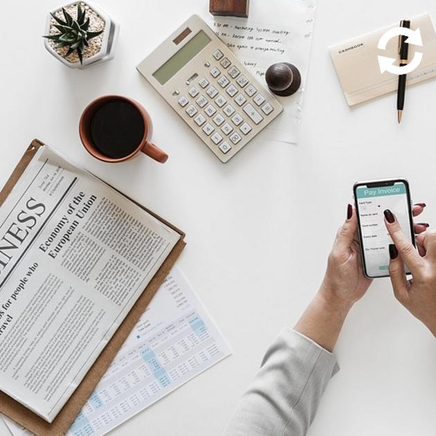 Personne utilisant son smartphone sur une table où sont déposés un journal, une tasse, une calculatrice, une enveloppe et un bic