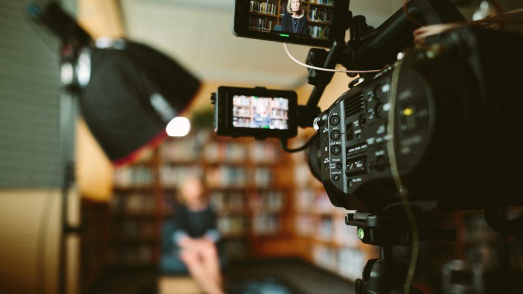 Caméra en avant plan filmant une personne assise au second plan